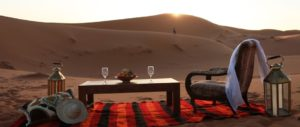 A picnic, including a table, red blanket, and wine glasses, set up among the dunes of a Moroccan desert