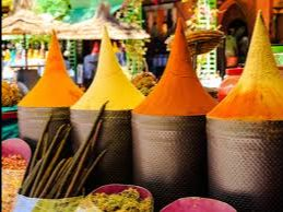 Four bright yellow and orange cones of spices located in a traditional Moroccan spice market