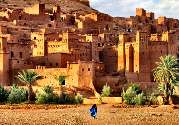 A human figure dressed in blue juxtaposed against traditional Moroccan architecture in the distance