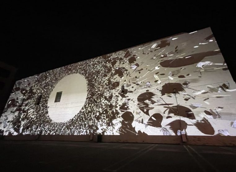 Digital art projected on a large wall outside