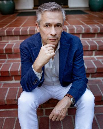 Alexander Nemerov, a white male with dark grey hair, sitting on brick steps