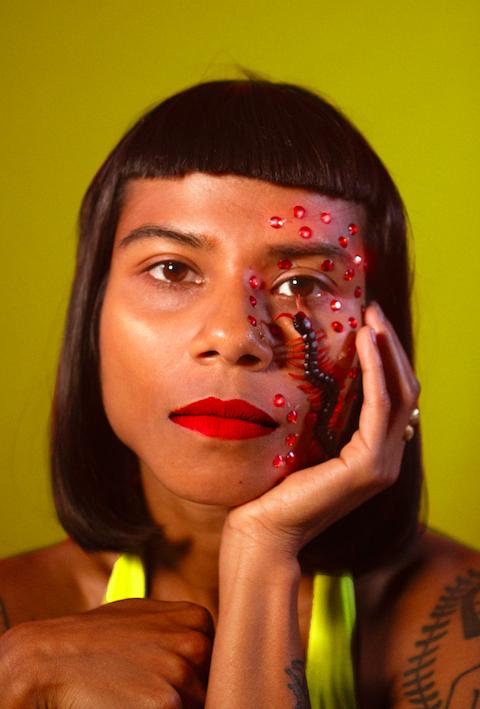 Headshot of Opashona Gosh against a dark yellow background