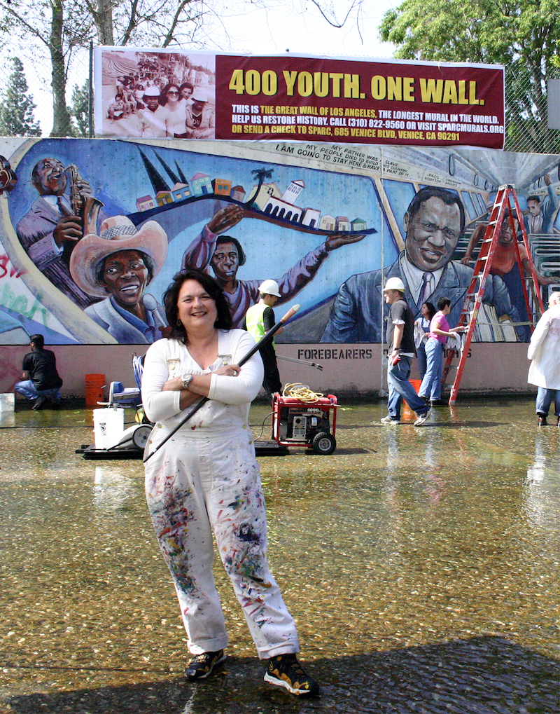 Judy Baca in a white jumpsuit in front of the Great Wall of Los Angeles